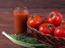 Red ripe tomatoes. In wicker basket with glass of tomato juice Stock Photography