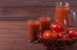 Red ripe tomatoes. In wicker basket with glass of tomato juice Royalty Free Stock Images