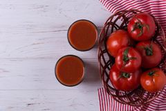 Red ripe tomatoes. In wicker basket with glass of tomato juice Royalty Free Stock Photo