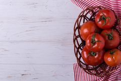 Red ripe tomatoes. In wicker basket on white background Royalty Free Stock Images