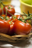 Red ripe tomatoes on the vine in a basket Royalty Free Stock Images