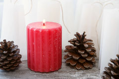 Red rippled candle among white blanks candles Stock Photography