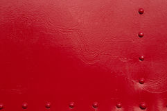 Red Rivets. A red painted metal background Royalty Free Stock Photography
