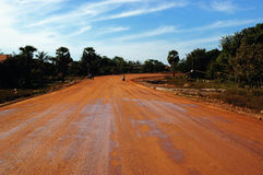 Red road. A red earth road in combodia Stock Photos