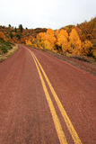 Red road in autumn scenery Royalty Free Stock Image