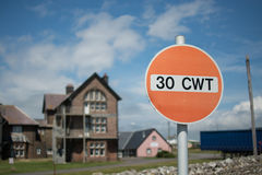 Red road sign indicating max weight. A red road sign, indicating maximum of 30 CWT, hundredweight, with an old abandoned building in the background Royalty Free Stock Photo