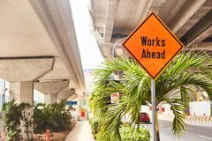Red road sign `Works Ahead` close up stock photography