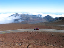 Red Road to the Volcano. A red car passes by red rocks on the way to Haleakala Volcano, an extinct volcano on Maui in Hawaii stock photos
