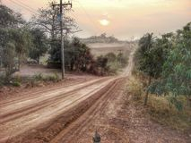 Red road under the sunrise in the valley Royalty Free Stock Photography