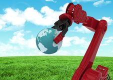 Red robot claw holding globe against green grass field and sky. Digital composition of red robot claw holding globe against green grass field and sky Stock Photos