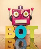Ronbot head bot. Red robot head and the word BOT on a wooden floor with reflection Royalty Free Stock Photo