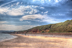 Red rock beach Dawlish Warren Devon England on a summer day in HDR. Having walked from the rocks stock image