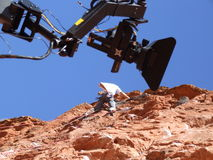 Red rock camera. Rock-climber on red rock with movie camera on a jib in the shot Royalty Free Stock Images