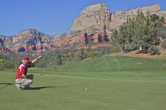 Red Rock Country Golfing. Golfer lines up his putt on a scenic green amongst the red rock country of sedona arizona Stock Photo
