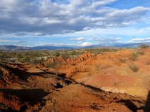 Red rocky hills and cloudy blue sky Stock Images