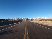 Red Rock Highway. Open highway leading to frost covered sandstone cliffs in Southern Nevada Stock Image