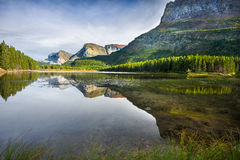 Red Rock Lake. Red rocks, pine trees, and clear reflecting water at Red Rock Lake in Glacier National Park, Montana on a late summer afternoon Royalty Free Stock Image
