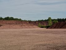 Red Rock Quarry Gravel Pit With Cliff. Landscape of red rock quarry gravel pit with piles of stone and cliff in background stock photography