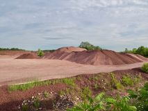 Red Rock Quarry Gravel Pit Landscape. Landscape of red rock quarry gravel pit with piles of crushed stone and cliff in background stock images