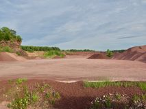 Red Rock Quarry Gravel Pit. Landscape of red rock quarry gravel pit with piles of stone and cliff in background stock photo