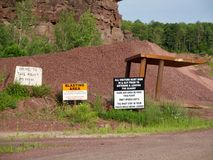 Red Rock Quarry Gravel Pit and Warning Signs. Landscape of red rock quarry gravel pit with piles of stone and cliff in background and warning signs stock image