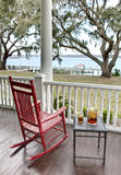Red rocking chair and iced tea. Red rocking chair and table with iced tea with waterfront view Royalty Free Stock Images