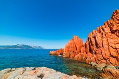 Red Rocks and blue sea in Rocce Rosse beach. Sardinia, Italy Stock Photos