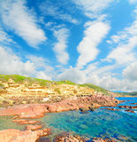 Red rocks and blue sea Stock Images
