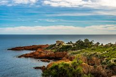 Stone house on red rocks coast Cote d Azur near Cannes, France stock image