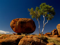 Red rocks of Devils Marbles. Devils Marbles in Australia, huge round red rocks next to eucalyptus tree royalty free stock photography