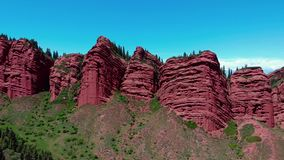 Red rocks with green grass shoot by drone