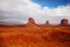 Red  rocks  intersect with rainbow. Red stone desert Navajo, USA. Isolated rocks - mitts intersect with the beautiful rainbow. On the road, the car is worth Royalty Free Stock Photography