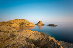 Red rocks and lighthouse of Ile Rousse in Corsica Royalty Free Stock Image