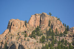 Giant Red Rocks in the Mountains. Red rocks in the mountains with trees on a sunny day Royalty Free Stock Photos