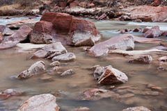 Red rocks on a river bed. Soft flowing water in Zion's National Park, UT Stock Photography