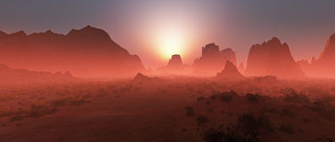 Red rocky desert landscape in the mist at sunset. Royalty Free Stock Image
