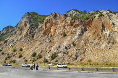 Red, rocky mountain cliffs along the road cars Kemer - Antalya in Turkey Royalty Free Stock Photography