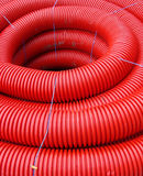 Red rolled up wire pipe on an industrial construction site Stock Photo
