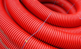 Red rolled up wire pipe on an industrial construction site Stock Photography