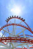 Red roller coaster rail with blue sky in background Stock Photography