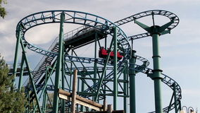 Red roller coaster running in its tracks. Containing people who wants to experience a thrill in the park stock footage