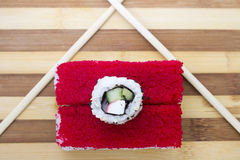 Red rolls with chopsticks on a cutting board Royalty Free Stock Photo