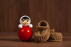 Red roly-poly doll and crochet baby booties Stock Photo
