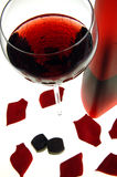 Red romance. A glass of red wine, rose petals and dark chocolates royalty free stock image