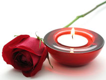 Red Romance. A burning tealight candle in a glass holder and a red rose. Photographed on white background royalty free stock image