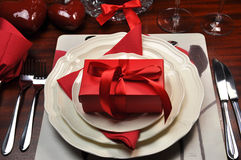 Red Romantic Dinner Table Setting with Gift Stock Photo