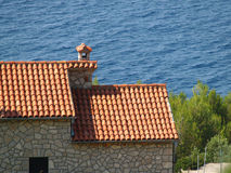 Red roof. Of small cottage against sea Stock Photography