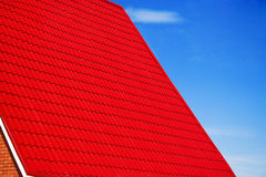 Red roof on the blue sky. House facade Royalty Free Stock Image