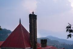 Red roof and chimney of a building shot against mountains and a. Building with a red conical roof and a brick chimney shot against mountains and a blue cloudy Stock Images
