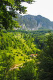 Red roof house hidden in the beautiful mountains of Romania Stock Image